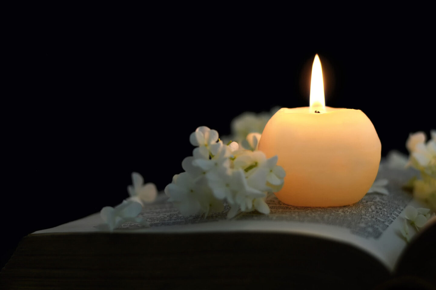 Burning,Candle,And,White,Flowers,On,Opened,Book
